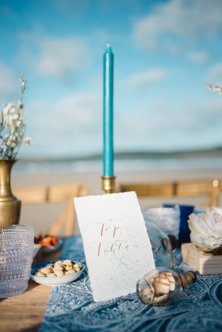 The table settign was decorated with turquoise candles and with done with a printed blue tablecloth