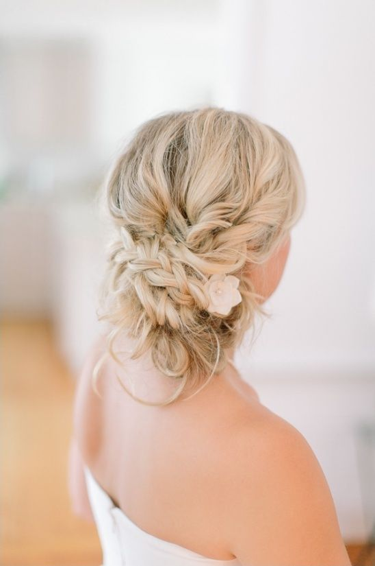 a braided messy low updo with a flower tucked inside and some little curls