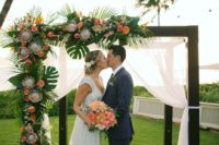 11 a dark stained arch with tropical leaves, peachy pink blooms and king proteas