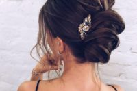 11 a gorgeous messy chignon with messy volume on top, locks down and a bold rhinestone hairpiece