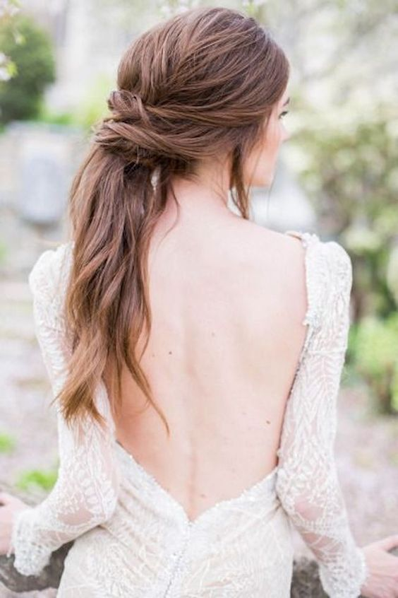 a low twsited and textural ponytail with some locks down and waves for an effortlessly chic look