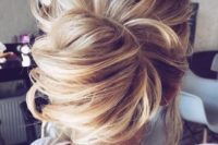 11 a messy and dimensional low bun with textures and some locks down is a romantic and trendy idea