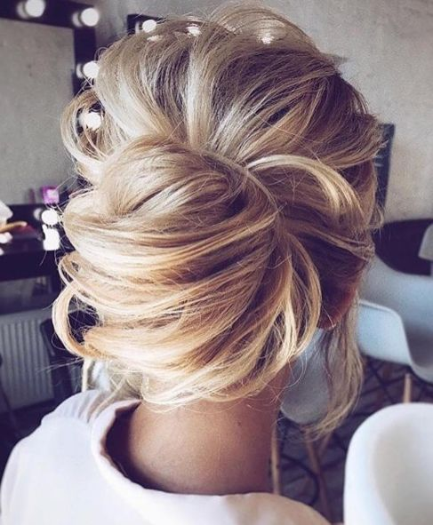 a messy and dimensional low bun with textures and some locks down is a romantic and trendy idea