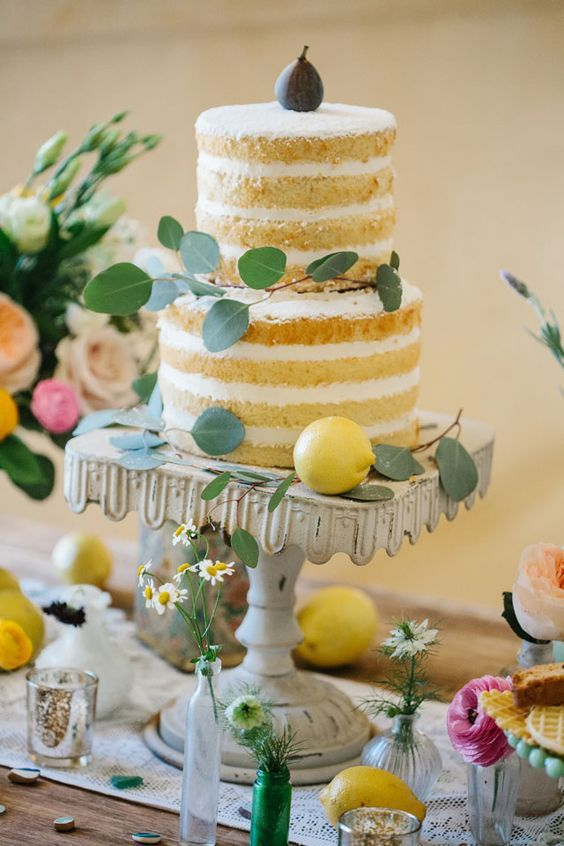 a naked wedding cake decorated with eucalyptus, lemons and a fig for a Mediterranean wedding