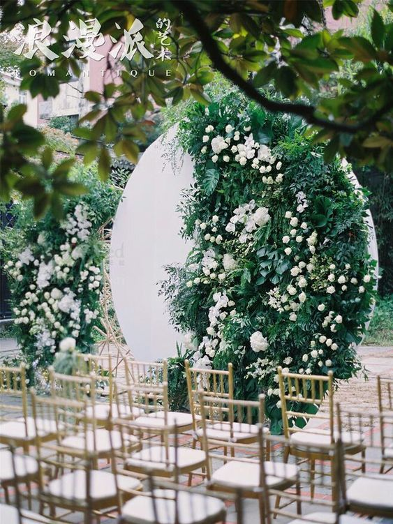 a round white backdrop with lush greenery and white blooms is a unique modern idea to make the space edgy