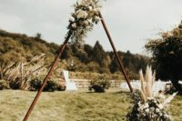 11 a wooden triangle arch with pampas grass, greenery and white blooms plus a candle lantern