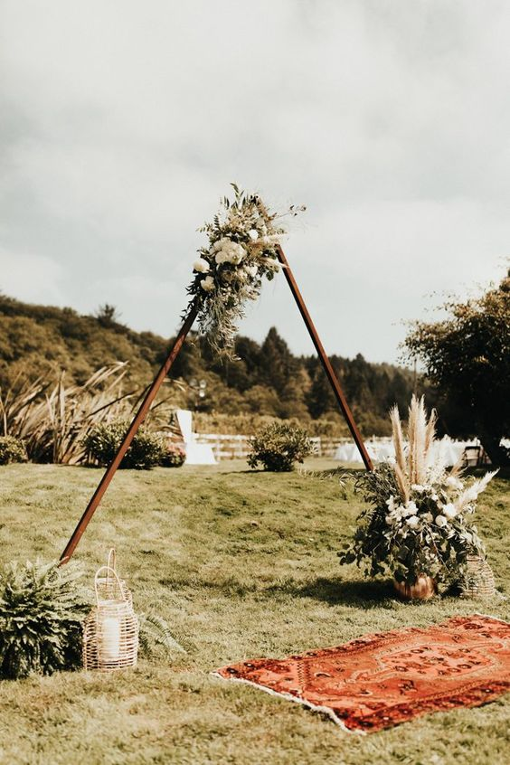 a wooden triangle arch with pampas grass, greenery and white blooms plus a candle lantern