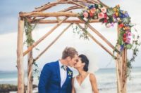 11 branch wedding arch decorated with colorful blooms and succulents for a tropical beach wedding