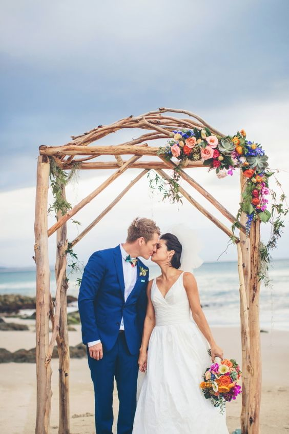 branch wedding arch decorated with colorful blooms and succulents for a tropical beach wedding