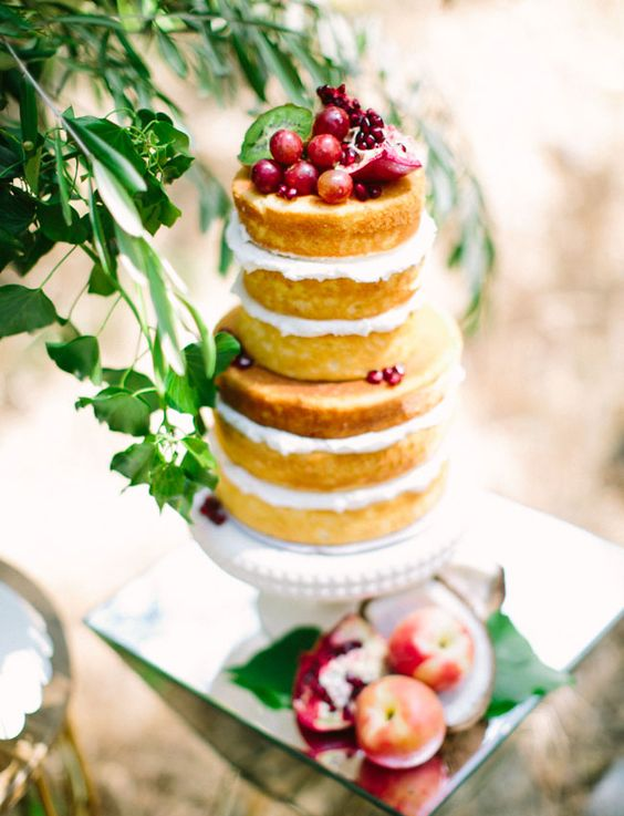 a naked wedding cake topped with pomegranates, grapes and cherries for a boho wedding