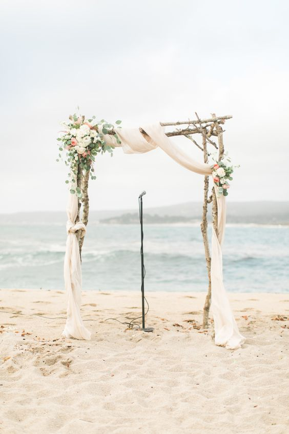 a rustic beach wedding arch with airy fabric, white and peachy blooms and eucalyptus