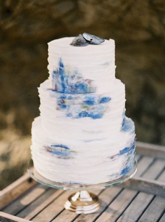 a unique watercolor ruffled wedding cake with some oyster shells on top