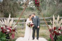 12 a wooden triangle arch with greenery and plum-colored blooms, with pampas grass and plum blooms at the base and a fur rug