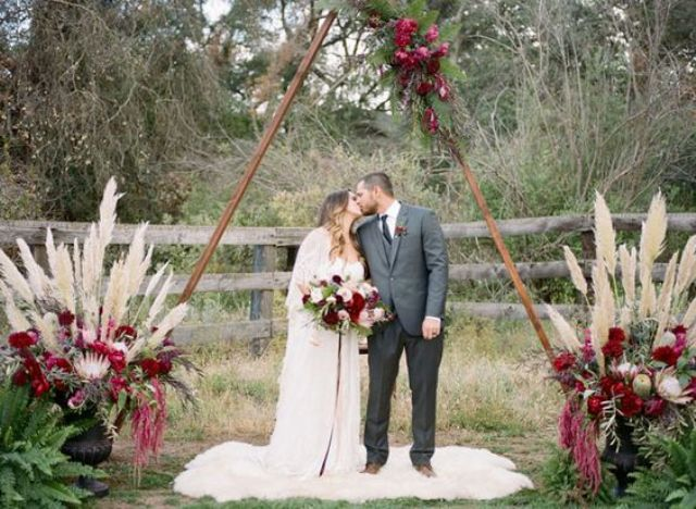 a wooden triangle arch with greenery and plum-colored blooms, with pampas grass and plum blooms at the base and a fur rug