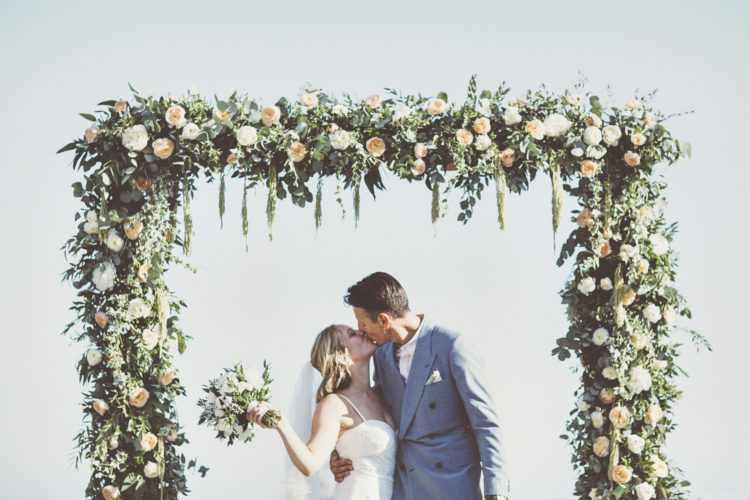 The wedding arch was mad eof greenery and peachy blooms, and th esea was the backdrop