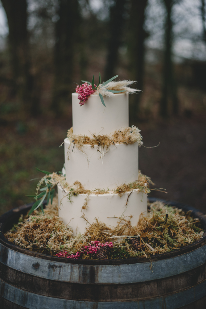 The white wedding cake was decorated with dry herbs, berries and greenery