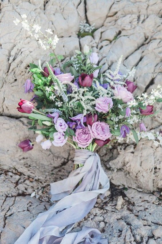 a colorful coastal wedding bouquet with lilac, purple and burgundy blooms plus herbs