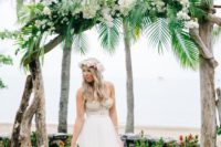 13 a driftwood wedding arch with tropical greenery and white blooms