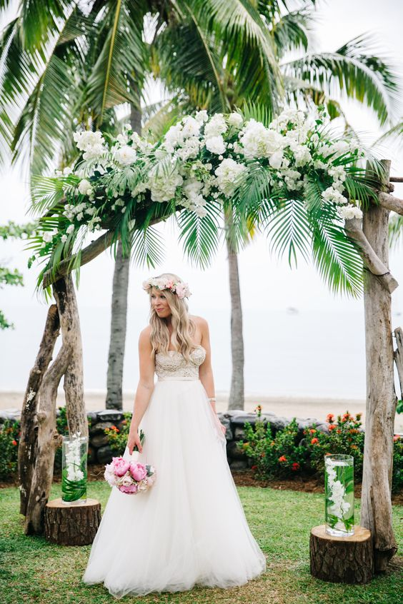 a driftwood wedding arch with tropical greenery and white blooms