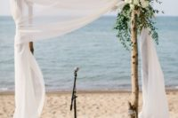 13 a rustic wedding arch with airy fabric, white flowers and greenery on the corner