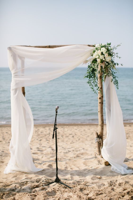 a rustic wedding arch with airy fabric, white flowers and greenery on the corner