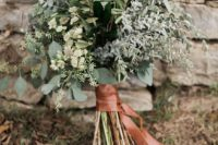 14 a greenery bouquet of various kinds of pale greenery and herbs with a copper leather wrapping for a modern bride