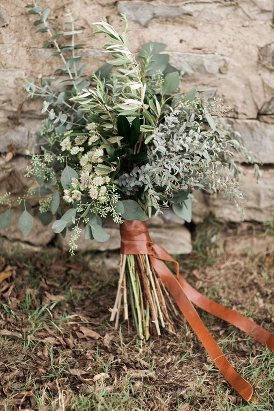 a greenery bouquet of various kinds of pale greenery and herbs with a copper leather wrapping for a modern bride