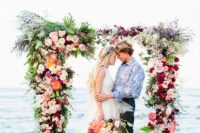 14 a super lush and romantic wedding arch with fuchsia, blush, orange and lilac blooms and greenery