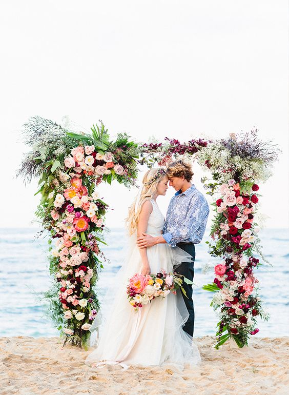 a super lush and romantic wedding arch with fuchsia, blush, orange and lilac blooms and greenery