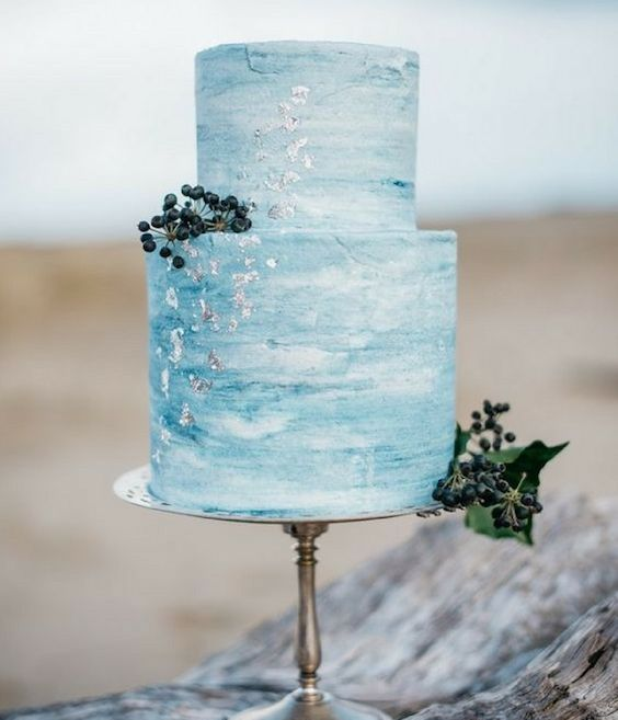 a watercolor blue wedding cake with silver leaf and some berries for a chic seaside wedding