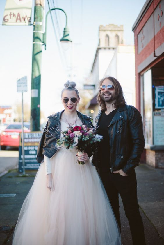 the bride in a black leather studded jacket and the groom in a black leather jacket too