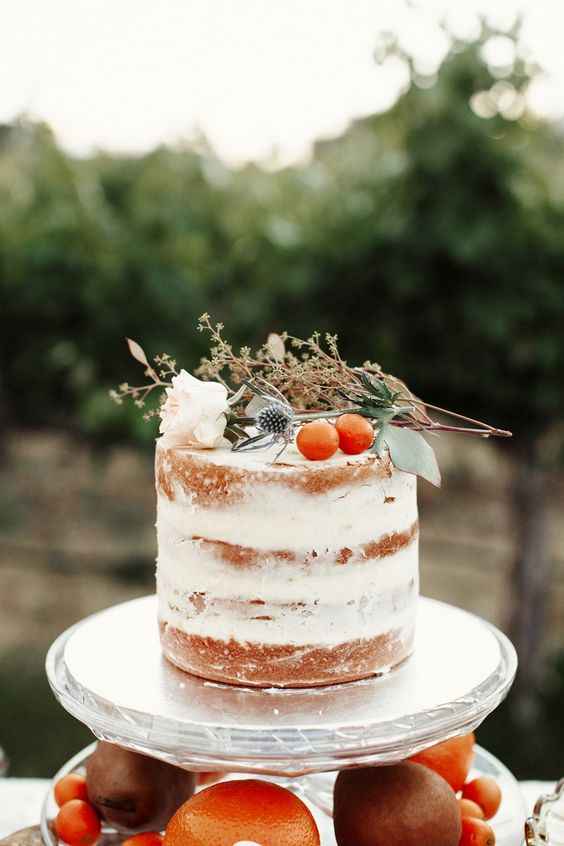 a naked wedding cake with thistles, a white bloom and kumquats, serve it with matching cupcakes