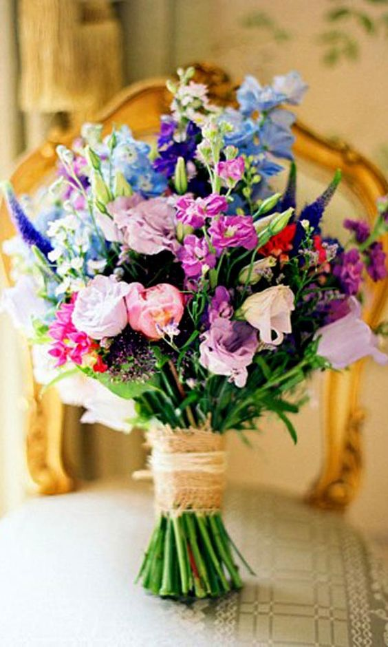a super colorful wedding bouquet in purple, mauve, blue, red and pink with a burlap wrap for a bold wedding
