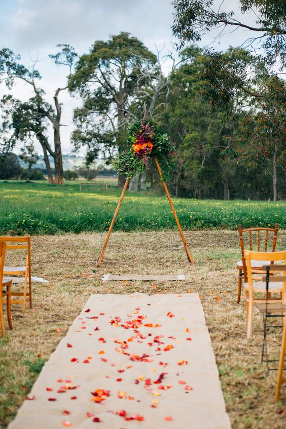 a triangle wedding arbow topped with lush cascading greenery and bold blooms in burgundy and orange for a fall wedding