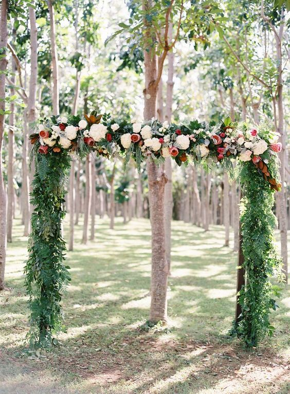 a tropical wedding arch with greenery, pink proteas and white blooms