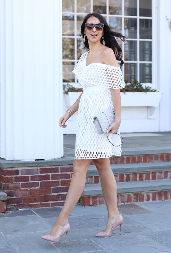 a white perforated one shoulder dress, blush shoes and a neutral bag