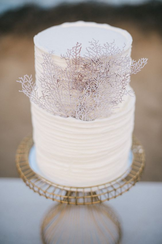 a white ruffled wedding cake decorated with corals is a stylish way to pull of a beach look
