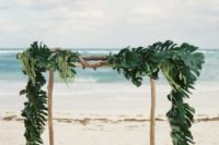 15 a wooden wedding arch covered fully with palm leaves for tropical beach decor
