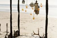 16 a boho beach ceremony arbor covered with black fabric with Moroccan lanterns and candle holders hanging