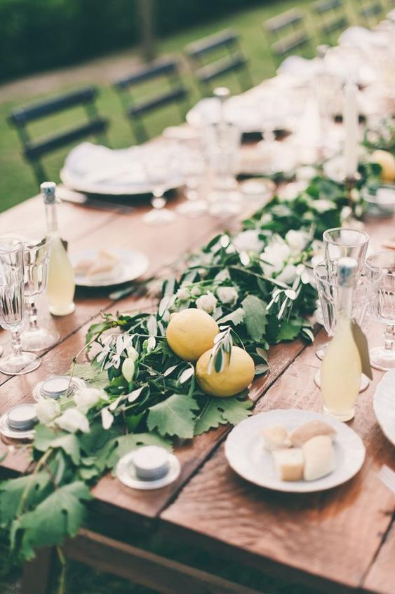 a greenery table runner with some lemons for a bold and fresh summer feel, add Limoncello as gifts