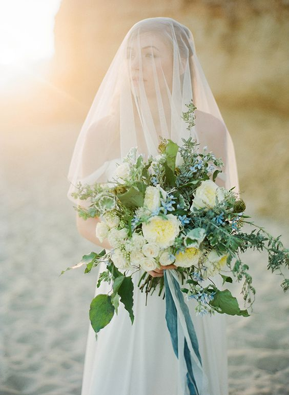 a large textural bouquet with neutral and blue flowers and greenery plus ribbons