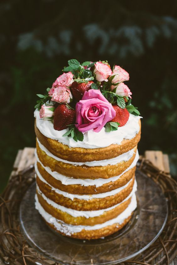 a naked wedding cake with whipped cream, fresh strawberries and pink roses for a garden summer wedding