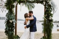 16 a wedding arch done with palm leaves, textural greenery and white blooms for a tropical beach wedding