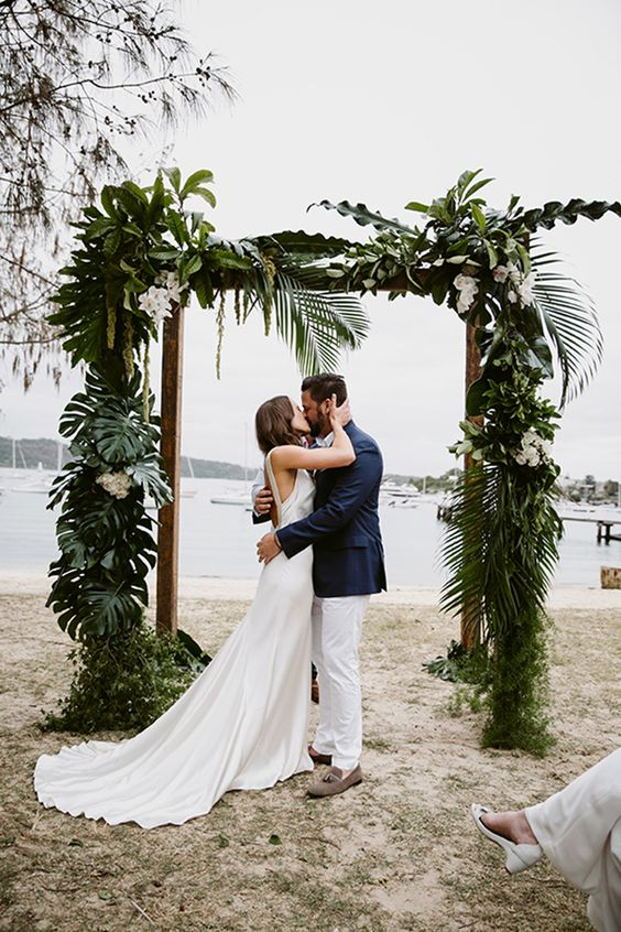 a wedding arch done with palm leaves, textural greenery and white blooms for a tropical beach wedding