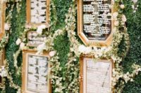 17 a greenery wall with vintage mirrors and greenery garlands as a unique and refined seating chart