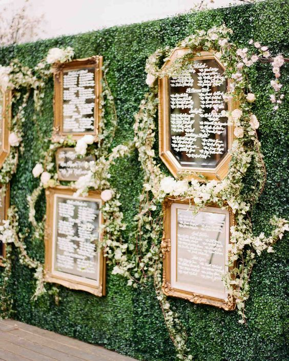 a greenery wall with vintage mirrors and greenery garlands as a unique and refined seating chart