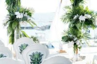 17 a tropical wedding arch covered with tropical leaves and with white orchids in tall vases