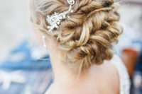17 a twisted low updo on long hair with a rhinestone hairpiece on one side for a refined look