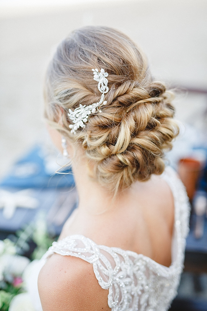 a twisted low updo on long hair with a rhinestone hairpiece on one side for a refined look