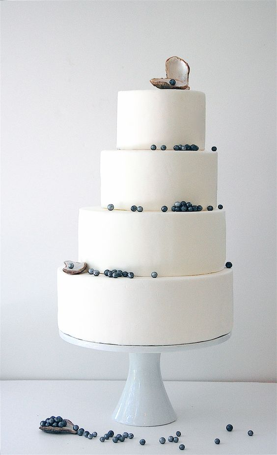 a beautiful white seaside wedding cake with blueberries as dark pearls and sugar shells